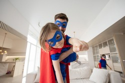 Father holding son flying in superhero costume at home