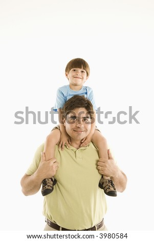 Father holding son on shoulders standing against white background.