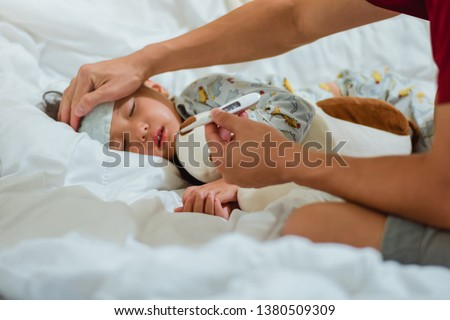 father holding thermometer foreground of sick little girl in bedroom at night time for monitor high fever with thermometer for ,Kid had high fever and tepid sponging to bring the temperature down Stockfoto ©