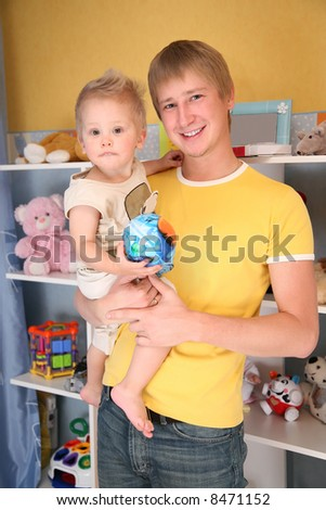 father holds child on hands in playroom