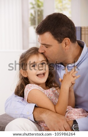 Father hugging and kissing little daughter, smiling. - stock photo