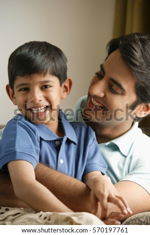father hugging son on couch, son smiles at camera