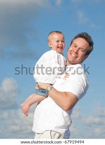 Father hugs baby smiling in the sun against a blue sky