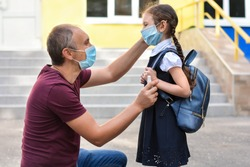 Father in a medical mask and with an antiseptic in his hands puts on a protective mask for his daughter against the background of the school. Back to school after covid-19 outbreak.