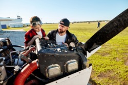father in black pilot jacket and his son in red shirt and aviator glasses, checking together motor cabinet before the flight on their private white light single-engine airplane.
