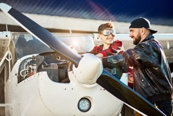 Father in black pilot jacket and son in red shirt and aviator glasses standing together above opened motor cabinet, checking light airplane before the flight. Outdoor shot.