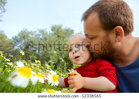 father in early thirties gives his son a kiss on the cheek in the flower field