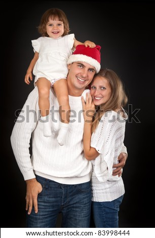 Father in santa hat holding little girl on his shoulder and hugged his wife in the studio against a dark background