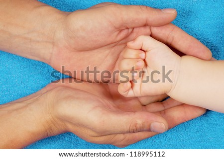 Father is holding baby's hand in his palms