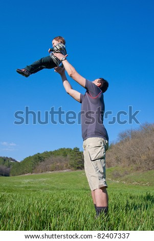 Father is playing with his 1.5 year son on the meadow