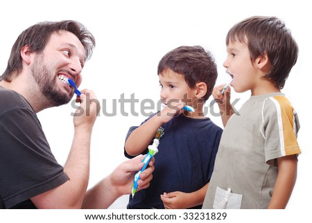 Father is teaching his son hot to clean the teeth properly