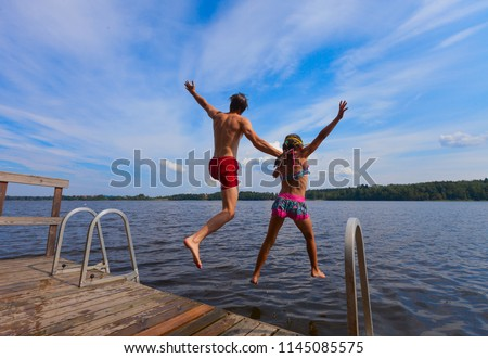 Father jumping into water with daughter. Young man together with girl diving from pier. Summer time sport activity. - Shutterstock ID 1145085575