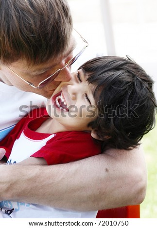 Father kissing his son, three years old - stock photo