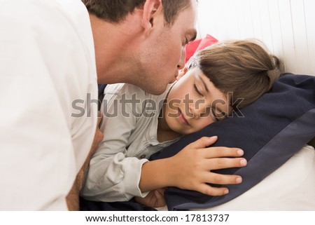Father kissing son goodnight
