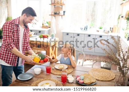 Father laughing. Father laughing while his cute funny daughter taking tomato for breakfast #1519966820
