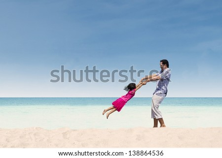 Father lifting her daughter on the beach