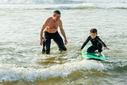 Father looking at son surfing on board. Happy father helping little son in wetsuit standing and swimming on surfboard on waves. Surfing concept