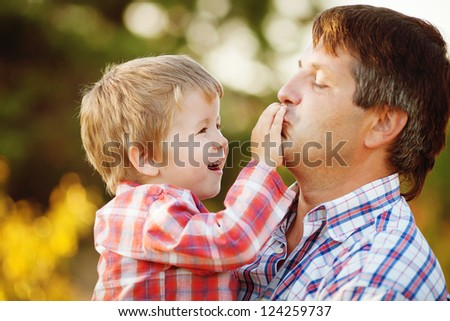 Father lying on grass smiling as son climbs on his back and hugs his neck - Summer holidays
