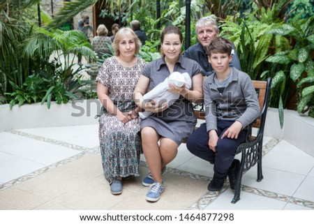 Father making picture with his family sitting on bench with newborn infant, adult woman carry a child in arms, son and grandparents are around
