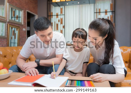 Father man mother helping their children to do their homework in their living room