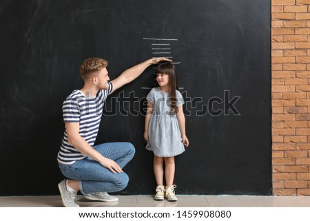 Father measuring height of his little daughter near wall with marks