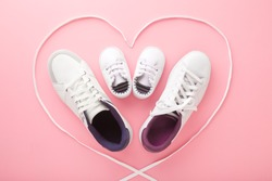 Father, mother and little kid shoes. Heart created from white shoelaces. Light pink floor background. Pastel color. New family. Love sport together concept. Closeup.