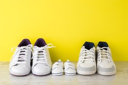 Father, mother and little kid white sport shoes on wooden floor at bright yellow wall. New family. Closeup.
