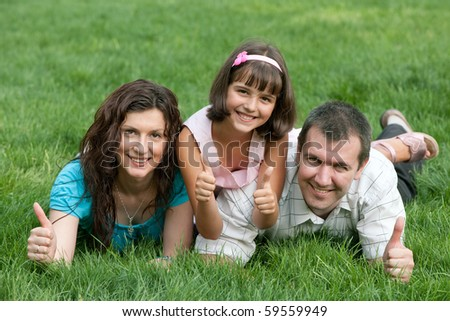Father, mother and their daughter are lying on the green grass holding  thumbs up