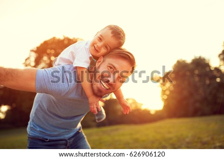 Father piggyback his little son outside