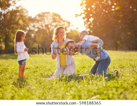 Father piggyback young boy in green nature  #598188365