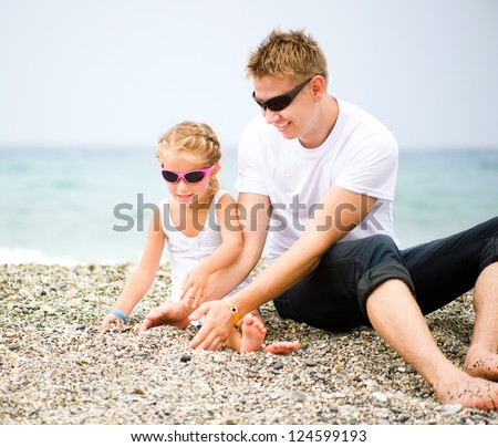 father play with his  daughter on the beach