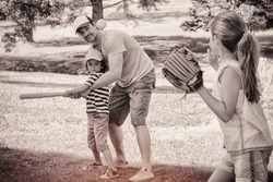 Father playing baseball with his children
