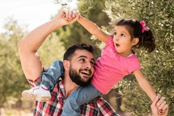 Father playing with daughter near to olive tree
