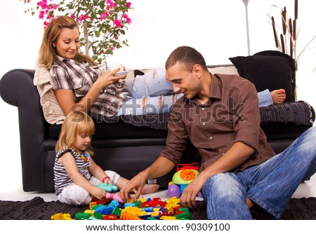 Father playing with daughters while mom relaxes with coffee