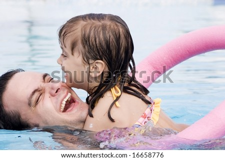 Father playing with his daughter in swimming pool - stock photo