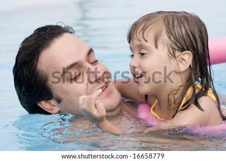 Father playing with his daughter in swimming pool