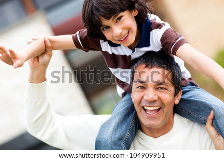 Father playing with his son carrying him on shoulders - stock photo