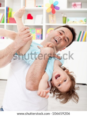 Father playing with toddler son lifting him in the air