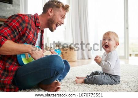 Father plays ukulele looking at young son at home, close up