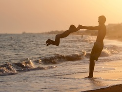 Father plays with his son on the beach at sunset