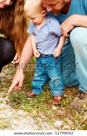 father pointing a rock to his toddler son in casual t-shirt and jeans on a nature walk with a mother