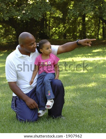 Father pointing out something interesting to daughter on knee. - stock photo