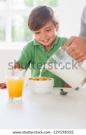 Father pouring milk in the cereal of his son in kitchen