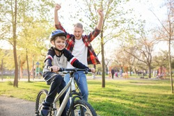Father proud of his son who learned to ride bicycle outdoors