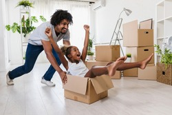 Father push cute little daughter sitting inside of carton box having fun riding in living room. Loan mortgage, housing improvement concept. Cheerful happy african family enjoy relocation day.