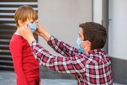 Father puts a medical mask on her son. Coronavirus, illness, infection, quarantine, medical mask, COVID19. Father, child wear facemask during coronavirus, flu outbreak. Dad with a son in medical mask.