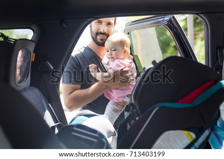 father putting his baby daughter into her car seat in the car