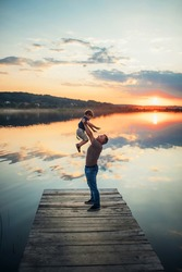 father raised his little son up standing on a wooden bridge against the background of a large lake and beautiful sunset in summer side view
