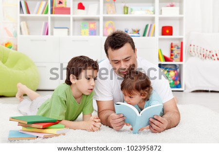 Father reading stories to his boy children at home
