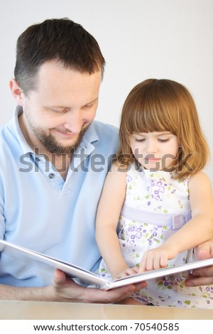 Father reading stories to his little daughter